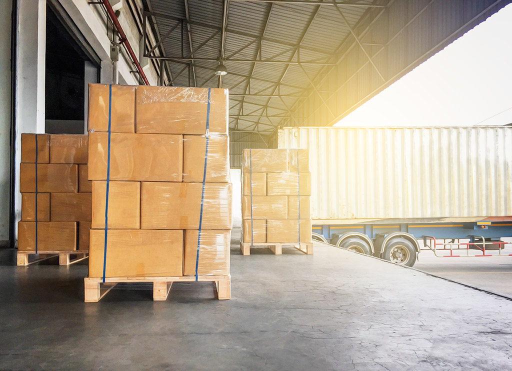 Stack of cardboard boxes on wooden pallet and truck docking at warehouse